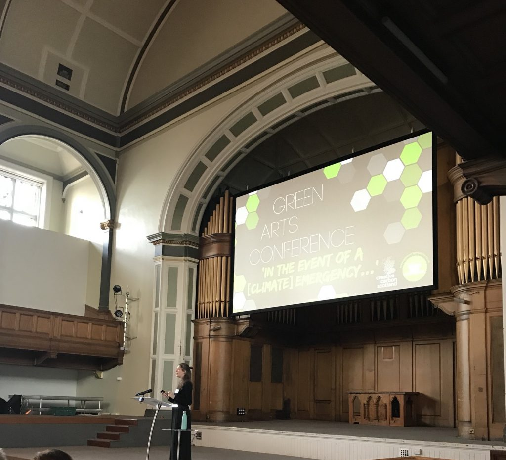 Photo of a woman at a podium in front of a powerpoint reading 'Green Arts Conference - In the Event of a Climate Emergency...'