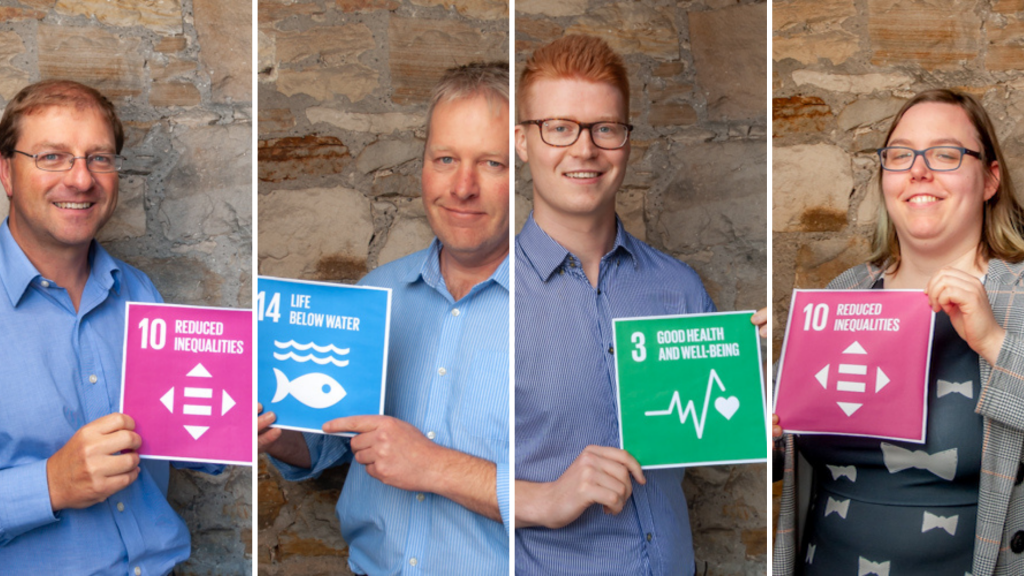Team photo of Paul, Donald, Oliver and Lisa holding up SDG signs